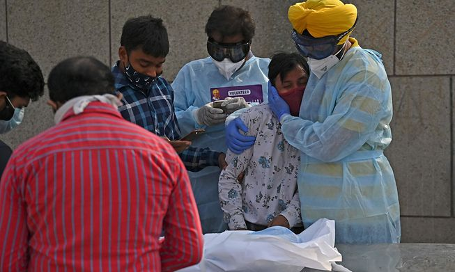 A man mourns over a child who died of Covid-19 at a crematorium in New Delhi on Wednesday.