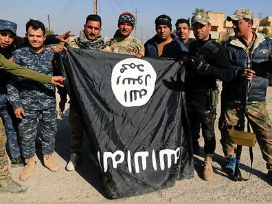 Iraqi security forces members pose with a seized Islamic State flag after driving out its miitants from Mosul's airport south west Mosul, Iraq, February 23, 2017. REUTERS/Zohra Bensemra
