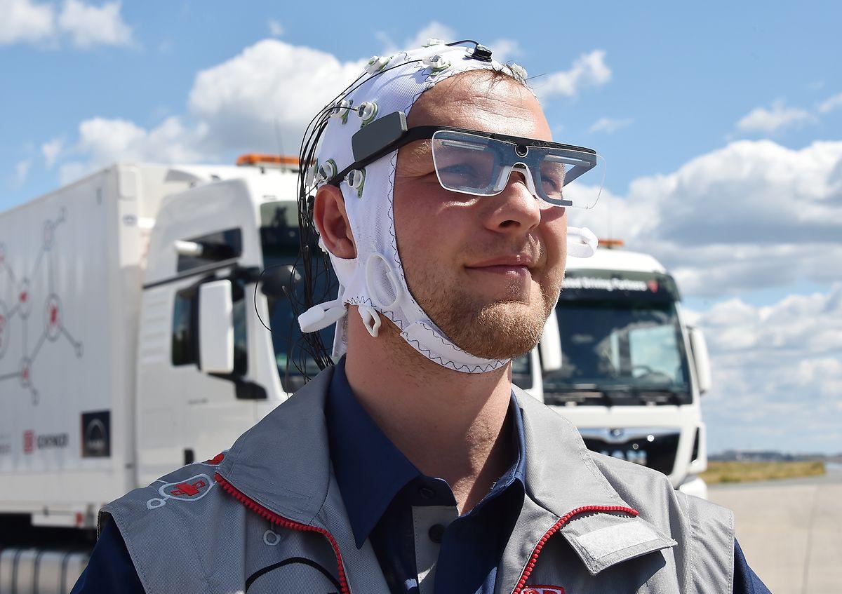 Ein Lastwagenfahrer trägt bei einer Demonstration des Platooning im autonomen Fahren auf der nichtgenutzten Südbahn des Flughafens Schönefeld ein Kontrollsystem mit dem mittels EEG und Eye Tracking die Auswirkungen des autonomen Fahrens auf Wachheit und Rollenverständnis des Fahrers ermittelt wird.