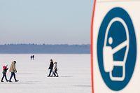 14.02.2021, Niedersachsen, Steinhude: Ein Schild weist auf die Maskenpflicht zur Eindämmung der Corona-Pandemie hin, während Menschen bei Sonnenschein auf dem zugefrorenen Steinhuder Meer unterwegs sind. Foto: Moritz Frankenberg/dpa +++ dpa-Bildfunk +++