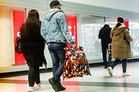 08.03.2021, Schleswig-Holstein, Norderstedt: Kunden gehen nach dem mehrwöchigen, coronabedingten Lockdown mit Einkaufstaschen durch das Herold-Center in Norderstedt. Im Gegensatz zur Nachbarstadt Hamburg können Kunden hier wieder in allen Geschäften ohne Voranmeldung einkaufen gehen. Foto: Markus Scholz/dpa +++ dpa-Bildfunk +++