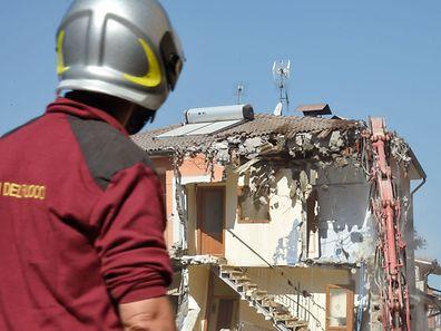Les pompiers ôtent à l'aide d'une grue les parties endommagées des bâtiments qui représentent une menace pour la sécurité des habitants. Ici au centre d'Amatrice.