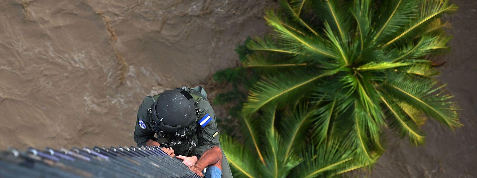 Aus einem Helikopter hat sich ein honduranischer Luftwaffen-Soldat abgeseilt, um einen Mann aus den Fluten des Chamelecon-Flusses zu retten.