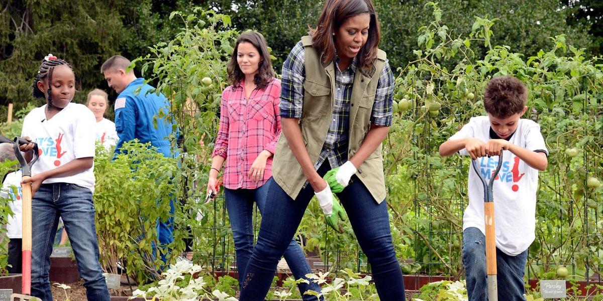 Michelle Obama greift zusammen mit Schülern zu Spaten und Harke.