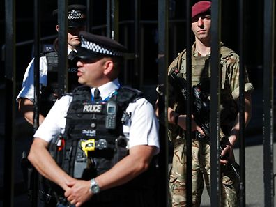 A British army soldier from the Parachute Regiment (R) stands alongside a police officer behind the gates to Downing Street, the official residence of Britain's Prime Minister, in central London on May 26, 2017, after Operation Temperer was put into force placing soldiers under police command on British streets in response to the May 22 terror attack at the Manchester Arena. Britain is hunting for a Libya-linked jihadist network thought to be behind the May 22 bombing at an Ariana Grande concert in Manchester, as US President Donald Trump threatened to prosecute anyone leaking details from the investigation to US media. / AFP PHOTO / Adrian DENNIS