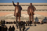 In a photo taken on December 17, 2020 people visit the statues of late North Korean leaders Kim Il Sung and Kim Jong Il on Mansu Hill on the occasion of 9th anniversary of Kim Jong Il's death, in Pyongyang. (Photo by KIM Won Jin / AFP)
