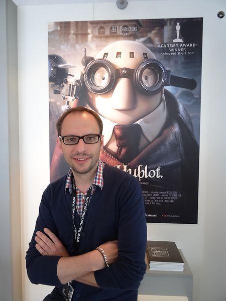 """Le producteur-réalisateur Laurent Witz devant l'affiche de son film à succès """"Mr Hublot"""" à Cannes en 2014."""