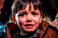 dpatopbilder - 01.03.2020, Griechenland, Lesbos: Ein Junge weint am Strand des Dorfes Skala Sikamias nach seiner Ankunft aus der Türkei mit einem Schlauchboot. Foto: Angelos Tzortzinis/dpa +++ dpa-Bildfunk +++