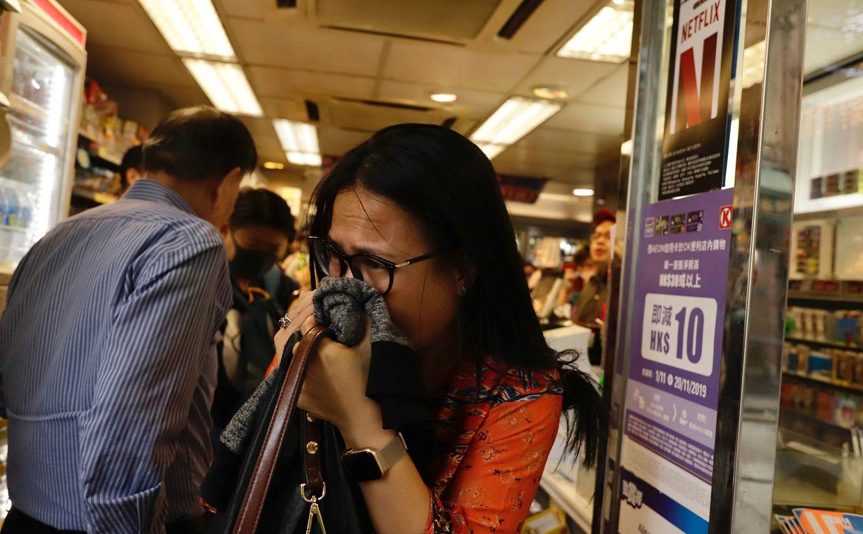 Eine Frau bedeckt beim Verlassen eines Geschäftes ihre Nase, nachdem Polizisten Tränengas während einer Demonstration vor dem Geschäft eingesetzt hat.