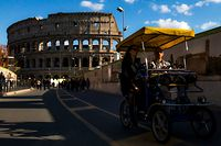 Tourists ride a rental four-wheeled bicycle in Rome by the Colosseum monument, which was closed along with some of the city's other landmarks and museums after the Italian government took drastic steps to stop the spread of the deadly coronavirus COVID-19 sweeping the globe, on March 8, 2020. (Photo by Laurent EMMANUEL / AFP)
