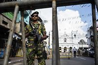"""A Sri Lankan soldier stands guard at a barricade near St. Anthony's Shrine in Colombo on April 28, 2019, a week after a series of bomb blasts targeting churches and luxury hotels on Easter Sunday in Sri Lanka. - Sri Lanka's Roman Catholic leader on April 28 condemned the Easter attacks as """"an insult to humanity"""" as the country marked a week since suicide bombers hit three churches and three luxury hotels. (Photo by Jewel SAMAD / AFP)"""