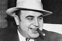 Infamous gangster Al Capone smokes a cigar on the train carrying him to the federal penitentiary in Atlanta where he will start serving an eleven-year sentence.