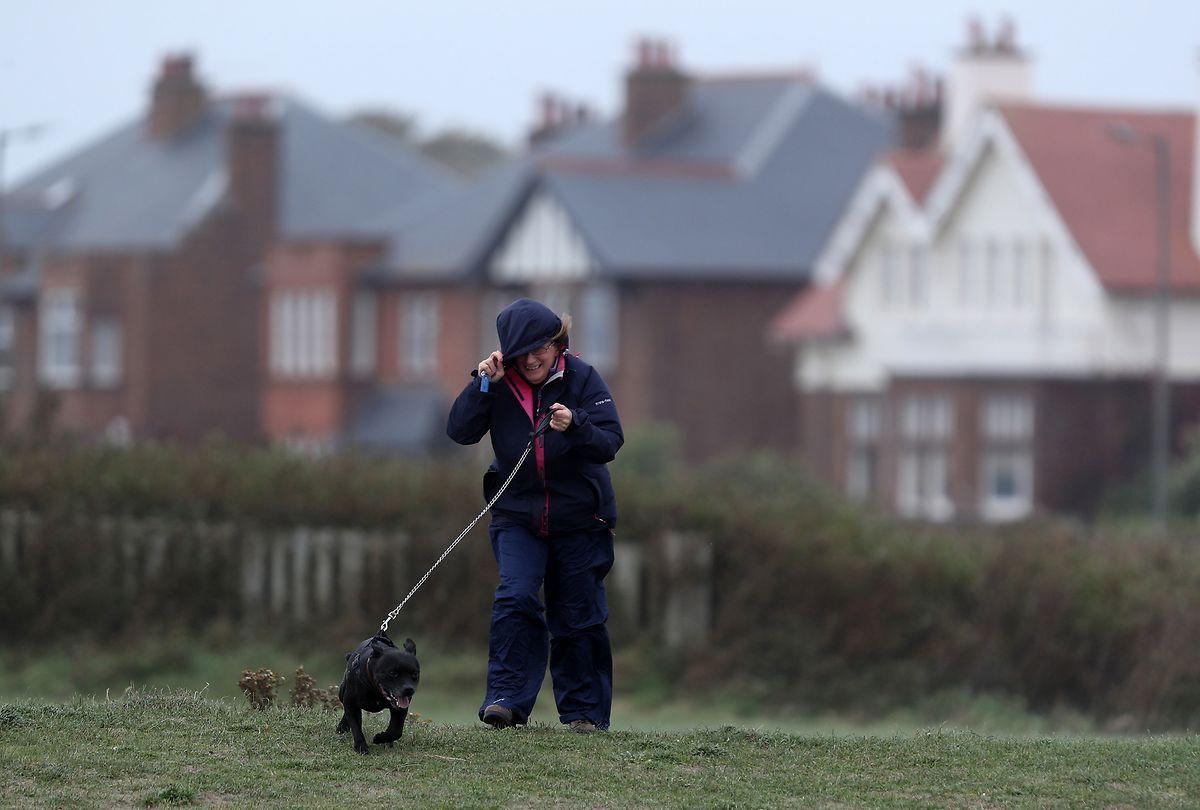 Großbritannien, Troon: Eine Frau geht bei starkem Wind mit ihrem Hund spazieren.