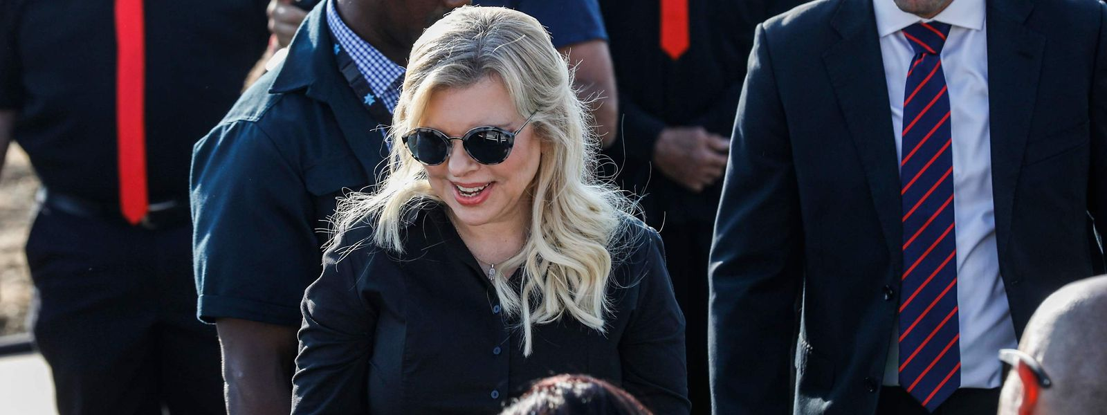 """Sara Netanyahu (C, front), wife of the Israeli Prime Minister, attends the unveiling ceremony for the new settlement of """"Ramat Trump"""", or """"Trump Heights"""" in English, named after the incumbent US President, in the Israeli-annexed Golan Heights on June 16, 2019 - Sara Netanyahu was on June 16 convicted of fraudulently using state funds for meals, under a plea bargain which dropped more severe charges. On the same day, her husband unveiled a """"Trump Heights"""" sign to mark the site of the new settlement, after the US president in late March recognised Israeli sovereignty over the part of the strategic plateau it seized from Syria in the 1967 Six-Day war. (Photo by Jalaa MAREY / AFP)"""