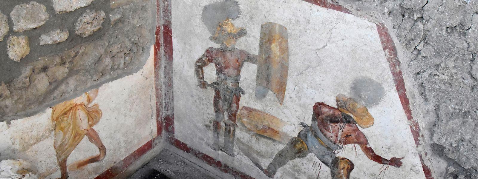 Zwei Gladiatoren sind auf einem Fresko zu sehen. Es zeigt zwei Kämpfer, der eine mit einem Schutzschild und einem Schwert. Der andere geht blutend zu Boden.