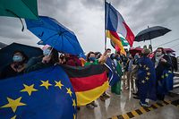 People holding European, French and German flags gather on the passerelle des Deux-Rives (footbridge of the Two Banks) connecting Strasbourg, France, to Kehl, in Germany, on June 14, 2020 on the eve of the reopening of the borders between France and Germany, after the two countries' measures to stop the spread of the COVID-19 pandemic caused by the novel coronavirus. (Photo by PATRICK HERTZOG / AFP)