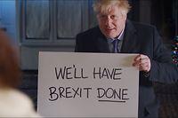 HANDOUT - 10.12.2019, Großbritannien, ---: Boris Johnson, Premierminister von Großbritannien, hält in einem Wahlwerbespot der Konservativen ein Schild mit der Aufschrift «We'll have Brexit done» («Wir werden den Brexit fertig kriegen»). Kurz vor der Parlamentswahl in Großbritannien hat Premier Johnson mit einer an den Liebesfilm «Love Actually» angelehnten Werbung gepunktet. Foto: -/Conservative Party/Press Association Images/dpa - ACHTUNG: Nur zur redaktionellen Verwendung im Zusammenhang mit der aktuellen Berichterstattung und nur mit vollständiger Nennung des vorstehenden Credits +++ dpa-Bildfunk +++