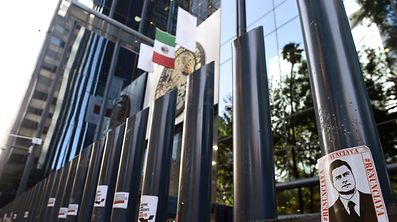 Stickers with the image of Mexican President Enrique Pena Nieto are stuck on columns outside the building of the attorney general's office during a protest against alleged government spying on journalists and human rights defenders in Mexico City on June 23, 2017.