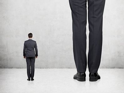 Rear view of two professionals in formal suites who stand in front of concrete wall.