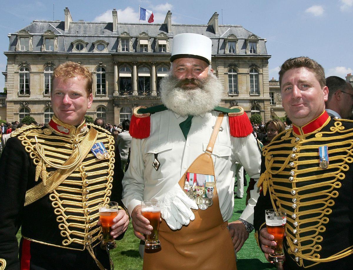 """Gartenparty im Elysée-Palast: Mitglieder der britischen """"Kings Troop Royal Artillery"""" genießen ihr Bier mit einem Kollegen aus der Fremdenlegion."""