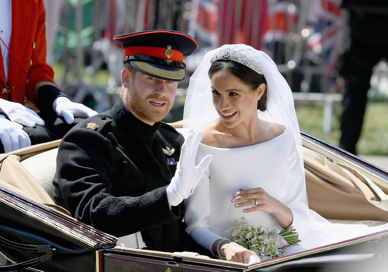 Britain's Prince Harry, Duke of Sussex and his wife Meghan, Duchess of Sussex wave from the Ascot Landau Carriage during their carriage procession on the Long Walk as they head back towards Windsor Castle in Windsor, on May 19, 2018 after their wedding ceremony.  / AFP PHOTO / POOL / Jeff J Mitchell