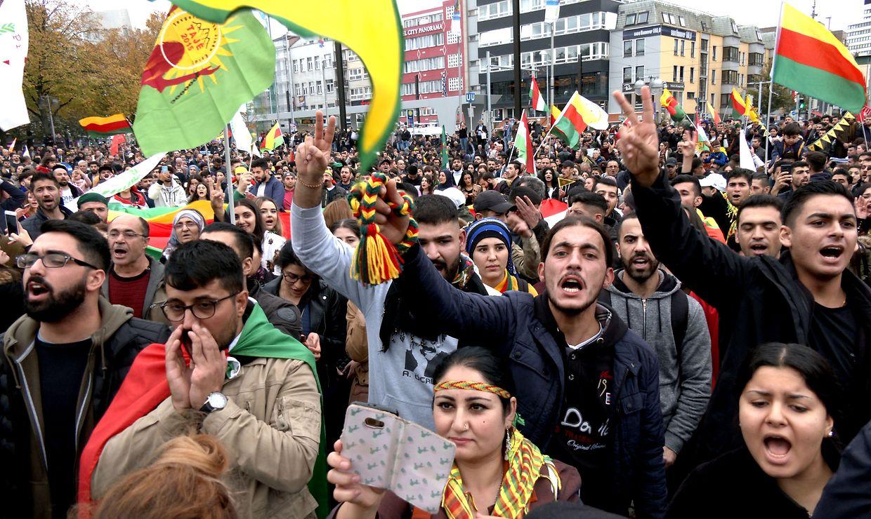Mit Plakaten und Fahnen demonstrieren Menschen in Hannover gegen den Angriff der türkischen Armee auf Nordsyrien.