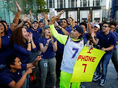 Jaime Gonzalez (C) celebrates with Apple workers after buying the iPhone 7 smartphone outside an Apple Inc. store in New York, U.S., September 16, 2016. REUTERS/Eduardo Munoz