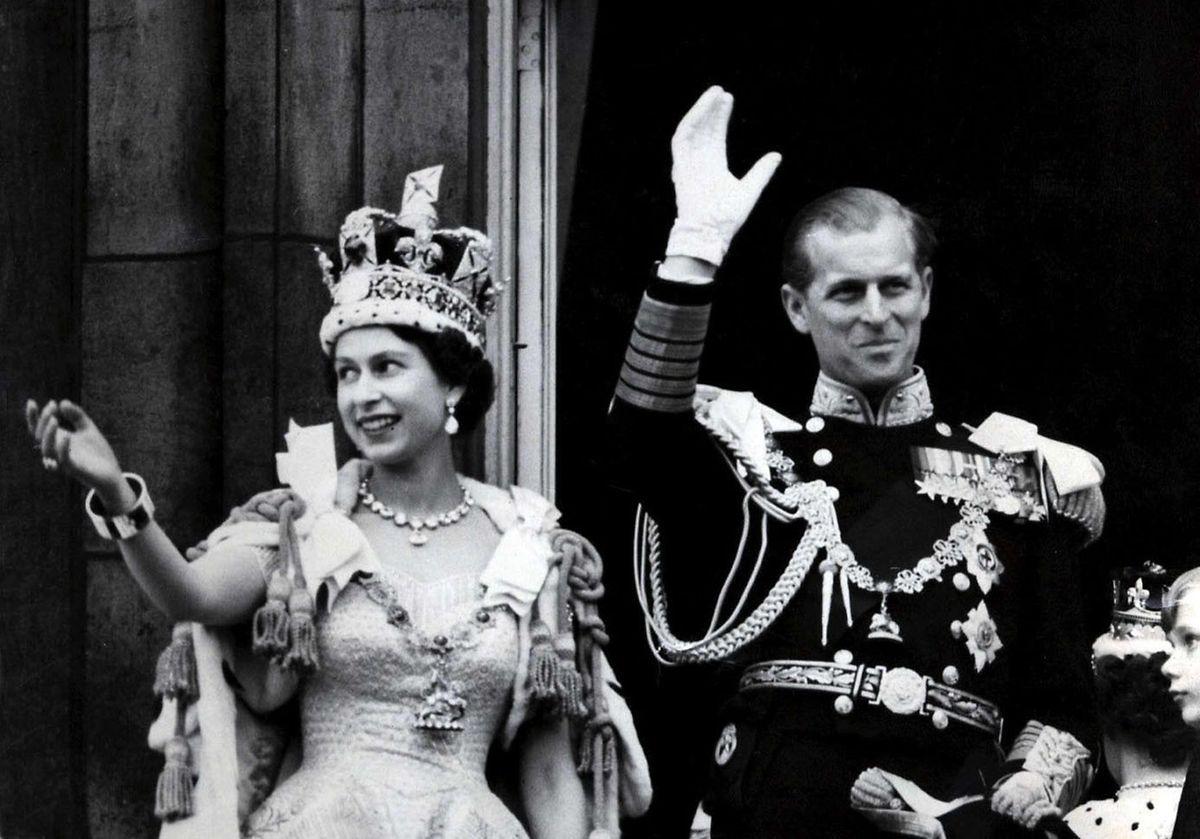 London, 1953: Königin Elizabeth ihr Mann Prinz Philip winken nach der prunkvollen Krönungszeremonie in der Westminster-Abtei vom Balkon des Buckingham Palasts den Menschen zu.