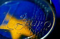 ARCHIV - 25.07.2012, Nordrhein-Westfalen, Köln: Die Fahne der Europäischen Union (EU) spiegelt sich in einer Euro-Münze. Der Euro sollte Europa einen - und sorgt doch immer wieder für Spannungen. Ist die Gemeinschaftswährung ein «Teuro» oder eine der wichtigsten Entscheidungen des Jahrhunderts?  (zu dpa «Friedensgarant und Spaltpilz: 20 Jahre Euro») Foto: Oliver Berg/dpa +++ dpa-Bildfunk +++