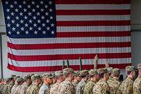 ARCHIV - 09.03.2017, Bayern, Illesheim: US-Soldaten stehen während einer militärischen Zeremonie in den Storck-Barracks vor einer Flagge der Vereinigten Staaten von Amerika. US-Präsident Donald Trump hat bestätigt, dass er die Zahl der US-Soldaten in Deutschland auf 25 000 reduzieren möchte. Trump sagte am Montag bei einer Veranstaltung im Weißen Haus zur Begründung, dass Deutschland nicht das Nato-Ziel für Verteidigungsausgaben erreiche Foto: Nicolas Armer/dpa +++ dpa-Bildfunk +++