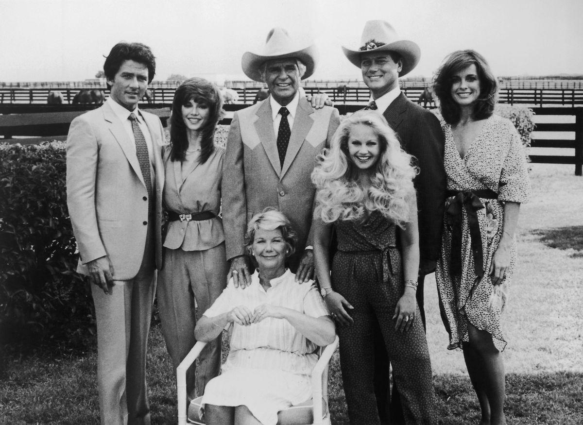 "Anfang der 1980er-Jahre am ""Dallas""-Set: Patrick Duffy, Victoria Principal, Jim Davis, Charlene Tilton, Larry Hagman und Linda Gray (stehend v.l.n.r.). Sitzend: Barbara Bel Geddes."