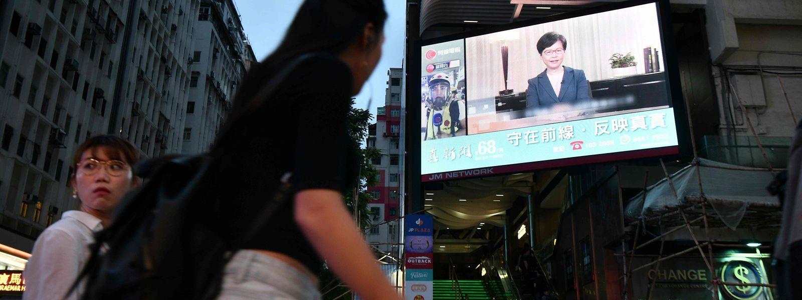Die Ansprache von Carrie Lam wird in Hongkong auf einem großen Bildschirm übertragen.