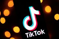 """FILES) This file photo taken on November 21, 2019 shows the logo of the social media video sharing app Tiktok displayed on a tablet screen in Paris. - TikTok star Anthony Barajas has died after being shot at a California movie theater in what authorities described as a """"random and unprovoked"""" attack. Barajas, 19, died on July 31, 2021 after the shooting that also killed his 18-year-old friend Rylee Goodrich, said police in Corona in southern California said The victims were shot Monday at a theater that was showing """"The Forever Purge,"""" about a totalitarian government that one night a year allows any crime to be committed, including murder. (Photo by Lionel BONAVENTURE / AFP)"""
