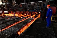 This picture taken on March 5, 2018 shows a Chinese employee watching red hot steel at a steel plant in Zouping in China's eastern Shandong province. A trade war with the US will benefit no one, China warned on March 8, adding it was prepared to give as good as it gets if US President Donald Trump fires the first shots. / AFP PHOTO / - / China OUT