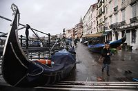 "Stranded gondolas are pictured washed away at Riva degli Schiavoni, after an exceptional overnight ""Alta Acqua"" high tide water level, early on November 13, 2019 in Venice. - Powerful rainstorms hit Italy on November 12, with the worst affected areas in the south and Venice, where there was widespread flooding. Within a cyclone that threatens the country, exceptional high water were rising in Venice, with the sirocco winds blowing northwards from the Adriatic sea against the lagoon�s outlets and preventing the water from flowing back into the sea. At 22:40pm the tide reached 183 cm, the second measure in history after the 198 cm of the 1966 flood. (Photo by Marco Bertorello / AFP)"