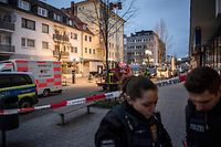 TOPSHOT - Police and emergency service are seen behind a police cordon near a bar (L) in the centre of Hanau, near Frankfurt am Main, western Germany, on February 20, 2020, after at least nine people were killed in two shootings late on February 19. - At least nine people were killed in shootings targeting shisha bars in Germany that sparked a huge manhunt overnight before the suspected gunman was found dead in his home early on February 20. The attacks occurred at two bars in Hanau, about 20 kilometres (12 miles) from Frankfurt, where armed police quickly fanned out and police helicopters roamed the sky looking for those responsible for the bloodshed. Police in the central state of Hesse said the likely perpetrator had been found at his home in Hanau after they located a getaway vehicle seen by witnesses. Another body was also discovered at the property. German counter-terror prosecutors said on February 20 they had taken over the investigation into two linked shootings. (Photo by Thomas Lohnes / AFP)