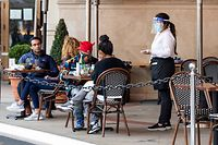 "A waitress takes customers' orders in the outdoor seating area of a restaurant on January 28, 2021 in Los Angeles. - California lifted blanket ""stay-at-home"" orders across the US state on Jaunary 25, paving the way for activities such as outdoor dining to return even in worst-hit regions as the pandemic's strain on hospitals begins to ease. (Photo by VALERIE MACON / AFP)"