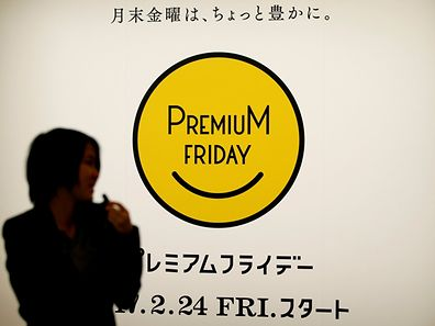 A woman walks past the logo of Premium Friday campaign, encouraging firms to let workers out a few hours early on the last Friday of every month so that they spend money on shopping and leisure to help boost the economy, in Tokyo, Japan, February 21, 2017. Picture taken February 21, 2017.   REUTERS/Toru Hanai