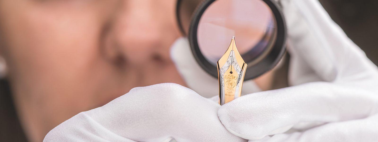 Mit Liebe zum Detail: Die Kontrolle in der Federfertigung wird von den Mitarbeiterinnen mittels einer Lupe vorgenommen. Nur einwandfreie Stücke werden dann mit dem Füllfederhalterkorpus zusammengefügt.