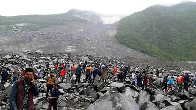 Chinese military police and rescue workers are seen at the site of a landslide in in Xinmo village, Diexi town of Maoxian county, Sichuan province on June 24, 2017.  Around 100 people are feared buried after a landslide smashed through their village in southwest China's Sichuan Province early Saturday, local officials said, as they launched an emergency rescue operation. / AFP PHOTO / STR / China OUT