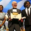 """Director Jacques Audiard (C), Palme d'Or award winner for his film """"Dheepan"""", actress Kalieaswari Srinivasan and actor Jesuthasan Antonythasan pose on stage during the closing ceremony of the 68th Cannes Film Festival in Cannes, southern France, May 24, 2015.                       REUTERS/Regis Duvignau"""