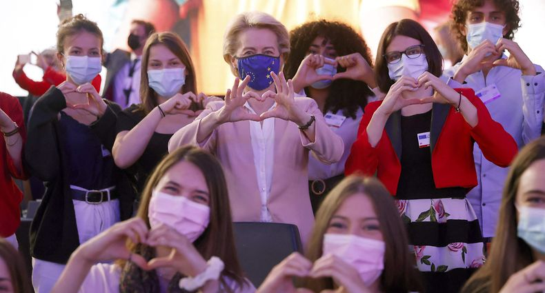 President of the European Commission Ursula von der Leyen (C) makes a heart with hands with Erasmus students during an Europe day ceremony and a Conference on the Future of Europe at the European Parliament in Strasbourg, eastern France, on May 9, 2021. (Photo by Jean-Francois Badias / POOL / AFP)