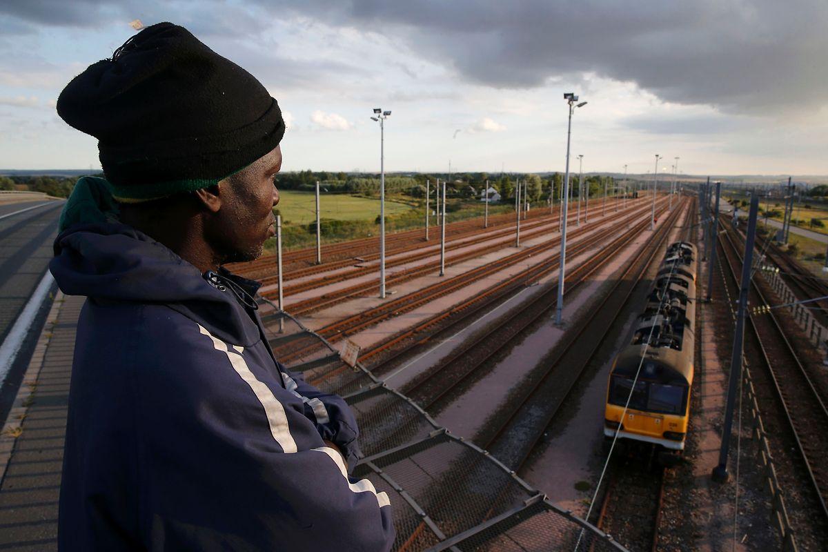Ein Migrant aus Rwanda schaut von einer Überführung in Calais auf einen vorbeifahrenden Zug hinab.