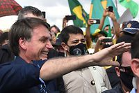 Brazil's President Jair Bolsonaro greets supporters upon arrival at Planalto Palace in Brasilia, on May 24, 2020, amid the COVID-19 coronavirus pandemic. - Despite positive signs elsewhere, the disease continued its surge in large parts of South America, with the death toll in Brazil passing 22,000 and infections topping 347,000, the world's second-highest caseload. (Photo by EVARISTO SA / AFP)