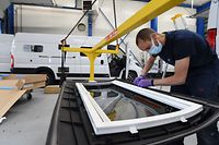 """Worker poses the gaskets prior installs a skyroof of a motorhome made from a Fiat """"Ducato"""" van, in the factory of the Pilote group, in Longuenee-en-Anjou, western France, on May 05, 2021. - With its 680 employees, two production sites in France and one in Germany, the Pilote Group, which builds 5,800 campervans and converted vans each year, became in 2020 the number 1 in France in terms of registration, in a boosted sector by the health crisis, which plunges the holidays under the sign of uncertainty (Photo by JEAN-FRANCOIS MONIER / AFP)"""
