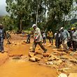 President Emmerson Mnangagwa (C) crosses a stream near Chimanimani Rural Hospital as he arrives to meet the survivors of Cyclone Idai, in Chimanimani on March 20, 2019. - International aid agencies raced on March 20, 2019 to rescue survivors and meet spiralling humanitarian needs in three impoverished countries battered by one of the worst storms to hit southern Africa in decades. Five days after tropical cyclone Idai cut a swathe through Mozambique, Zimbabwe and Malawi, the confirmed death toll stood at more than 300 and hundreds of thousands of lives were at risk, officials said. (Photo by ZINYANGE AUNTONY / AFP)