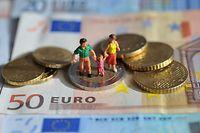 """ARCHIV- ILLUSTRATION - Ein Paar mit einem Kind steht auf einer Zwei-Euro-Münze, die auf Geldscheinen liegt, aufgenommen am 16.02.2011. Wegen hoher Mietkosten rutschen einkommensschwache Familien laut einer Studie in vielen größeren deutschen Städten, wie zum Beispiel Frankfurt, unter Hartz-IV-Niveau. Foto: Andreas Gebert dpa (zu dpa/lhe """"Studie: Nach Abzug der Miete viele arme Familien unter Hartz-IV"""" vom 22.07.2013) +++(c) dpa - Bildfunk+++"""