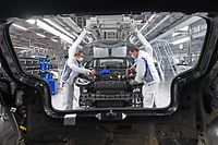 """EmployeesMax Bruehmann (L) and Heiko Gruner wear face masks as they work on the assembling of a Volkswagen ID.3 electric car at the plant of German car maker Volkswagen (VW) in Zwickau, eastern Germany, after production restarted on April 23, 2020 amid the novel coronavirus COVID-19 pandemic. - Some companies, such as car giant Volkswagen, have own step-by-step plans for reactivating production in Germany in the coming weeks. Preparations to reopen factories included """"a comprehensive catalogue of measures to protect workers' health"""", Volkswagen brand chief operating officer Ralf Brandstaetter had said before. (Photo by Hendrik Schmidt / POOL / AFP)"""