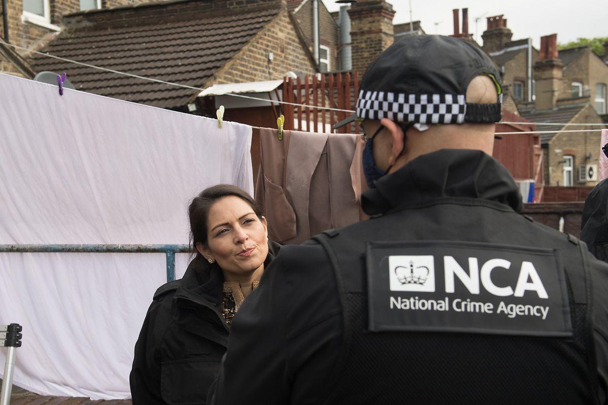 Priti Patel (l), Innenministerin von Großbritannien, nimmt an einem Einsatz der National Crime Agency im Osten Londons teil.