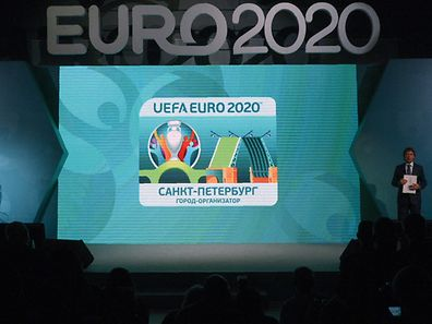 The UEFA EURO 2020 host city Saint Petersburg logo is seen on a screen during its launch in Saint Petersburg on January 19, 2017. The EURO 2020 UEFA European Championship will see matches hosted in 13 cities across Europe, with the semi-finals and final staged at Wembley Stadium in London in July 2020. / AFP PHOTO / Olga MALTSEVA